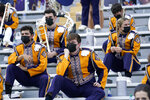 FILE - In this Sept. 26, 2020, file photo, members of the LSU marching band, wearing mask, sit socially distanced from one another due to COVID-19 restrictions before an NCAA college football game between the LSU and the Mississippi State in Baton Rouge, La. Louisiana State University students will have to wear masks in classrooms and at campus events this fall to help fight the spread of COVID-19, but won't have to be vaccinated to return to school, university officials announced Wednesday, Aug. 4, 2021. (AP Photo/Gerald Herbert, File)