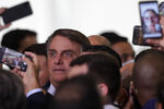 Brazil's President Jair Bolsonaro has his photo taken with newly elected mayors after a ceremony to present the government's agenda, at the Planalto Presidential Palace, in Brasilia, Brazil, Tuesday, Feb. 23, 2021. (AP Photo/Eraldo Peres)