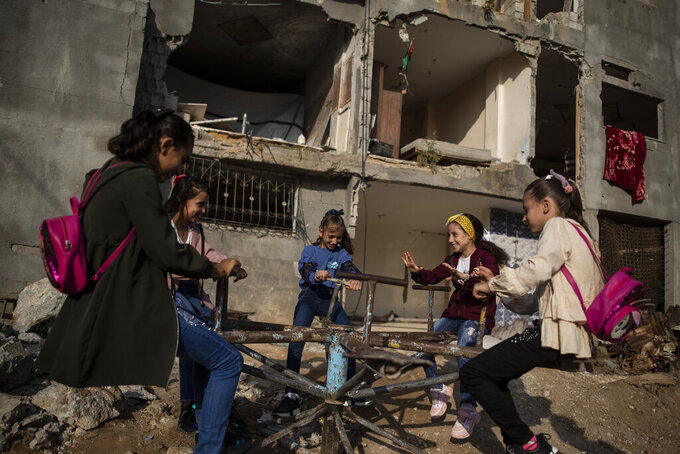 Young girls play in front of a destroyed house as they celebrate the first day of Eid al-Adha holiday in town of Beit Hanoun, northern Gaza Strip, Tuesday, July. 20, 2021. Eid al-Adha, or the festival of sacrifice, is celebrated by Muslims around the world to commemorate Prophet Ibrahim's test of faith. (AP Photo/Khalil Hamra)