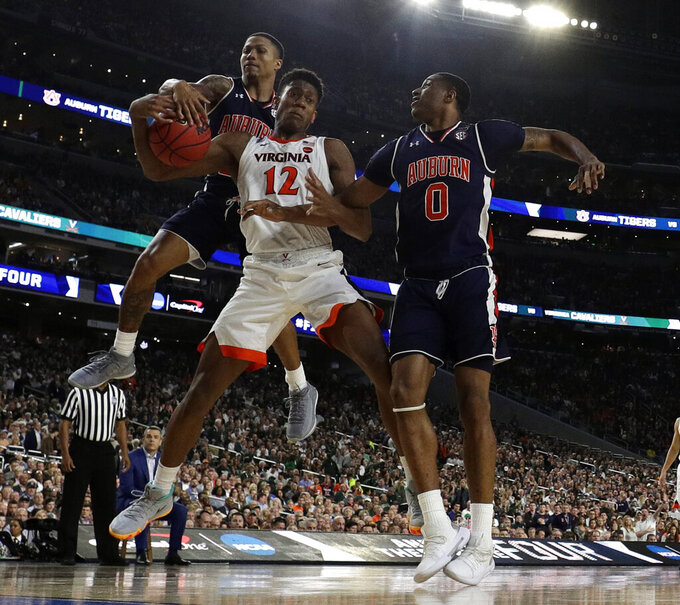 Virginia's De'Andre Hunter (12) battles for a rebound against Auburn's J'Von McCormick and Horace Spencer (0) during the second half in the semifinals of the Final Four NCAA college basketball tournament, Saturday, April 6, 2019, in Minneapolis. (AP Photo/David J. Phillip)