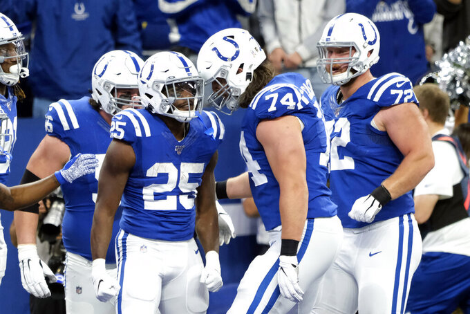 Indianapolis Colts running back Marlon Mack (25) celebrates his touchdown run with offensive tackle Anthony Castonzo (74) during the first half of an NFL football game against the Jacksonville Jaguars, Sunday, Nov. 17, 2019, in Indianapolis. (AP Photo/AJ Mast)