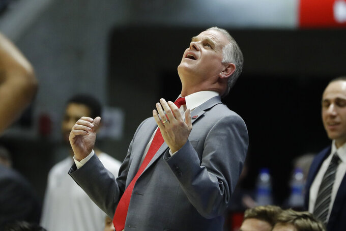 San Diego State coach Brian Dutcher looks up at a monitor during the first half of the team's NCAA college basketball game against Boise State, Saturday, Jan. 11, 2020, in San Diego. (AP Photo/Gregory Bull)