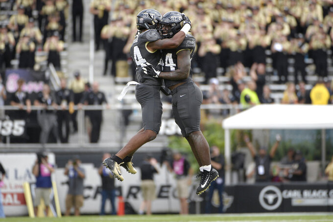 """FILE - In this Nov. 10, 2018, file photo, Central Florida linebacker Gabriel Luyanda, left, and linebacker Nate Evans celebrate after the team recovered a fumble during the first half of an NCAA college football game against Navy, in Orlando, Fla. No. 11 Central Florida has won 22 straight games and is making a run at another major bowl bid. ESPN's """"College GameDay"""" is coming to the schools' Orlando, Florida, campus this week. (AP Photo/Phelan M. Ebenhack)"""