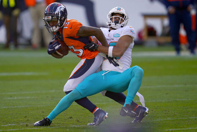 Denver Broncos wide receiver K.J. Hamler (13) is tackled by Miami Dolphins defensive back Nik Needham during the first half of an NFL football game, Sunday, Nov. 22, 2020, in Denver. (AP Photo/David Zalubowski)