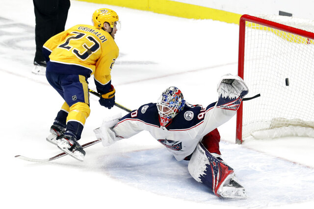 Nashville Predators right wing Rocco Grimaldi (23) scores the winning goal against Columbus Blue Jackets goaltender Elvis Merzlikins (90) in a shootout during an NHL hockey game Saturday, Feb. 22, 2020, in Nashville, Tenn. The Predators won 4-3. (AP Photo/Mark Humphrey)