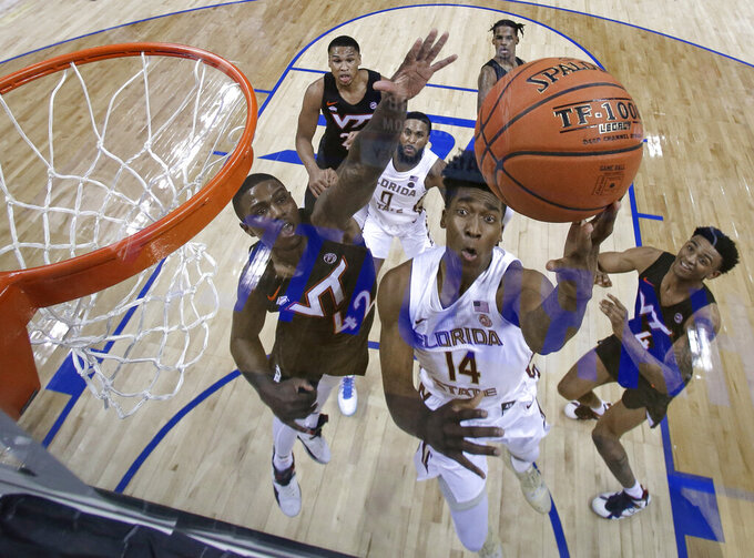 Florida State's Terance Mann (14) shoots against Virginia Tech's Ty Outlaw (42) and Nickeil Alexander-Walker (4) during the second half of an NCAA college basketball game in the Atlantic Coast Conference men's tournament in Charlotte, N.C., Thursday, March 14, 2019. (AP Photo/Chuck Burton)