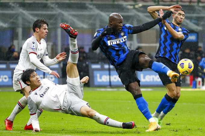 FILE - In this Dec. 5, 2020, file photo, Bologna's Takehiro Tomiyasu, left, and Inter Milan's Romelu Lukaku fight for the ball during a Series A soccer match between Inter Milan and Bologna, at Milan's San Siro Stadium. The photo was honored by the Associated Press Sports Editors as best sports action photo of 2020 at their annual winter meeting. (AP Photo/Antonio Calanni, File)