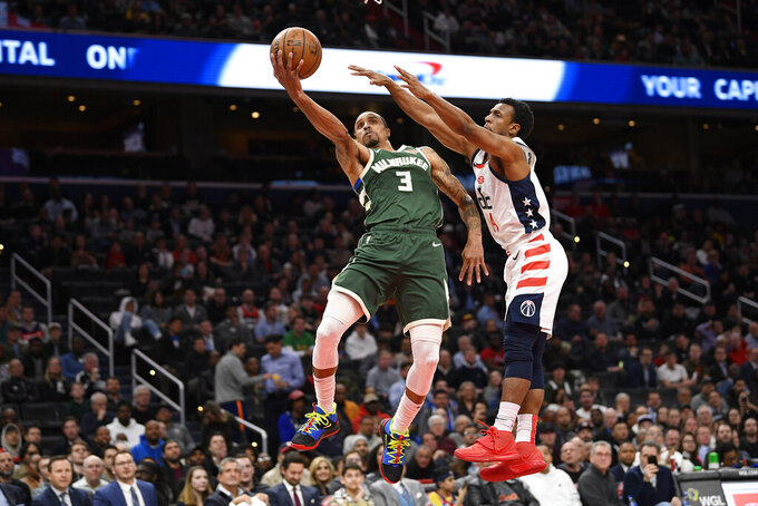 FILE - In this Feb. 24, 2020, file photo, Milwaukee Bucks guard George Hill (3) goes to the basket next to Washington Wizards guard Ish Smith (14) during the first half of an NBA basketball game in Washington. Hill was shooting 48% from 3-point range - well above his career average of 38.5% and light years better than his 2018-19 average of 28% - before the stoppage in play. The 34-year-old guard as well as teammate Donte DiVincenzo could be even bigger factors in the early part of the restart since Bucks teammates Eric Bledsoe and Pat Connaughton have tested positive for coronavirus, though both are now in Florida. (AP Photo/Nick Wass, File)
