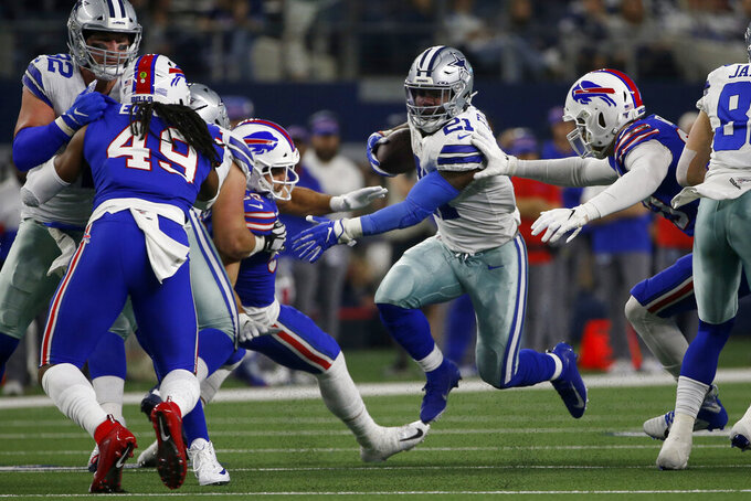Dallas Cowboys running back Ezekiel Elliott (21) runs the ball through Buffalo Bills linebacker Tremaine Edmunds (49) and other defenders in the first half of an NFL football game in Arlington, Texas, Thursday, Nov. 28, 2019. (AP Photo/Ron Jenkins)
