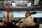 In this Friday, Aug. 23, 2019, photo, Fox Sports play-by-play announcer Joe Buck, left, and analyst Troy Aikman, right, work in the broadcast booth before a preseason NFL football game between the Miami Dolphins and Jacksonville Jaguars, in Miami Gardens, Fla. The exhibition game served as a dress rehearsal for the Fox Sports crew for the upcoming Super Bowl to be hosted by Miami in 2020. (AP Photo/Lynne Sladky)
