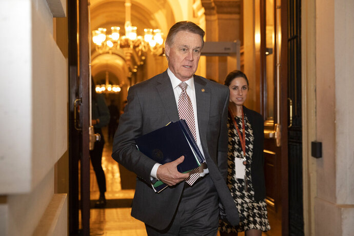"""FILE - In this Jan. 31, 2020, file photo, Sen. David Perdue, R-Ga., leaves Capitol Hill in Washington. Perdue has taken down a digital campaign ad featuring a manipulated picture of his Democratic opponent, Jon Ossoff, who is Jewish, with an enlarged nose. A spokeswoman for Perdue said in a statement Monday, July 27, 2020, that the image has been removed from Facebook, calling it an """"unintentional error"""" by an outside vendor, without naming the vendor. (AP Photo/Jacquelyn Martin, File)"""