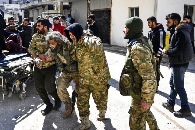 In this photo taken on Sunday, March 1, 2020, Turkey-backed opposition fighters help a fellow fighter wounded in fighting with Syrian government forces and their allies in Sarmin, south of Idlib, Syria. Fighting on the ground in Idlib continued Monday, with heavy clashes between Syrian government forces and Turkish-backed fighters. (AP Photo)