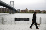 A dog walker passes a social distancing sign while wearing a protective mask at Domino Park, Friday, May 8, 2020, in the Brooklyn borough of New York. Some parks will see stepped-up policing to stem the spread of the coronavirus, New York City Mayor Bill de Blasio said Friday. He also announced that 2,500 members of a
