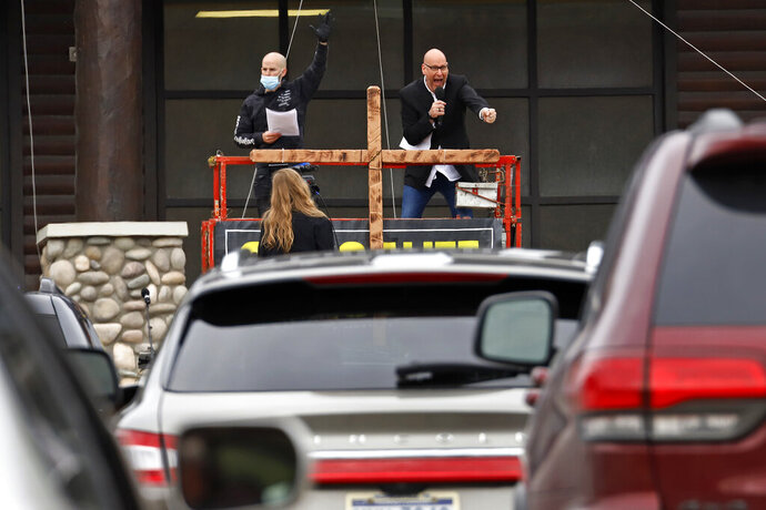 FILE - Paster Bruce Schafer, top right, preaches from a scissor lift during the first of two drive-in Easter services held by Grace Life Church in a parking lot in Monroeville, Pa., Sunday, April 12, 2020. The principle of religious freedom is important to most Americans. But as President Donald Trump touts his support for it during his reelection bid, there are notable fault lines among people of different faiths and political ideologies over what it truly means. (AP Photo/Gene J. Puskar, File)