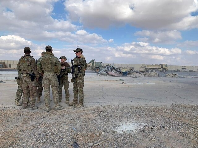 FILE - In this Jan. 13, 2020, photo, U.S. Soldiers stand while bulldozers clear rubble and debris at Ain al-Asad air base in Anbar, Iraq. Six Army soldiers who were injured in a ballistic missile attack in Iraq in January have been awarded Purple Hearts, and 23 others have been approved for the award and will get them later this week, U.S. Central Command said Monday. (AP Photo/Ali Abdul Hassan, File)