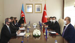 Turkey's Foreign Minister Mevlut Cavusoglu, right, and Azerbaijan Foreign Minister Ceyhun Bayramov speak during a meeting, in Ankara, Turkey, Tuesday, Aug. 11, 2020. (Cam Ozdel/Turkish Foreign Ministry via AP, Pool)