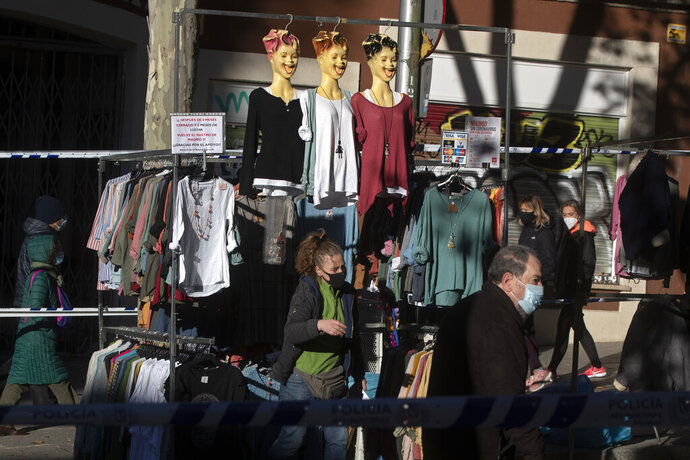 People walk by a clothes stall in the Rastro flea market in Madrid, Spain, Sunday, Nov. 22, 2020. Madrid's ancient and emblematic Rastro flea market reopened Sunday after a contentious eight-month closure because of the COVID-19 pandemic that has walloped the Spanish capital. (AP Photo/Paul White)