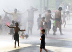 Children and adults escape 90 degree temperatures as they cool off in The Whirlpool Compass Fountain Friday, July 19, 2019, in St. Joseph, Mich.(Don Campbell/The Herald-Palladium via AP)