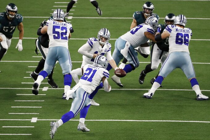 Dallas Cowboys running back Ezekiel Elliott (21) takes the hand off from quarterback Andy Dalton (14) in the second half of an NFL football game against the Philadelphia Eagles in Arlington, Texas, Sunday, Dec. 27. 2020. (AP Photo/Roger Steinman)