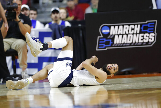 Nevada forward Caleb Martin falls to the court after getting fouled during a first round men's college basketball game against Florida in the NCAA Tournament, Thursday, March 21, 2019, in Des Moines, Iowa. (AP Photo/Charlie Neibergall)