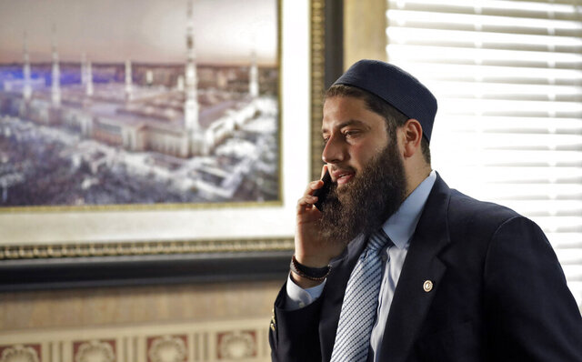 FILE - In this Feb. 20, 2019, file photo, Hassan Shibly,  speaks on a phone before a news conference in Tampa, Fla.   Alaa Massri, a Muslim woman arrested during protests on June 10, 2020 in Miami was allegedly forced to remove her religious head cover at a correctional center and her mugshot was taken without it, according to her lawyer.  Shibly, chief executive director of the Florida chapter of the Council on American-Islamic Relations, a Muslim civil rights and advocacy group, said mugshots of Massri without her hijab must be expunged and charges dismissed and called for the termination of involved officers.(AP Photo/Chris O'Meara, File)