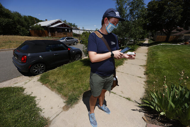 In this Wednesday, June 24, 2020, photo, Joey Prestley, a staff canvasser for the Progressive Turnout Project, uses hand sanitizer between stops to talk to voters in the age of the new coronavirus in northwest Denver. The coronavirus pandemic isn't going away anytime soon, but campaigns are still forging ahead with in-person organizing.  (AP Photo/David Zalubowski)