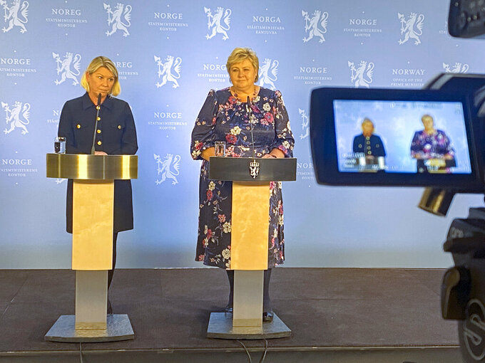 Norway's Acting Prime Minister Erna Solberg, right, and Minister of Justice Monica Mæland, left, speak at a press conference after the police briefing on the attack in Kongsberg, Norway, Wednesday, Oct. 13, 2021. A man armed with a bow and arrows killed several people Wednesday near the Norwegian capital of Oslo before he was arrested, authorities said. (Ole Berg-Rusten/NTB via AP)