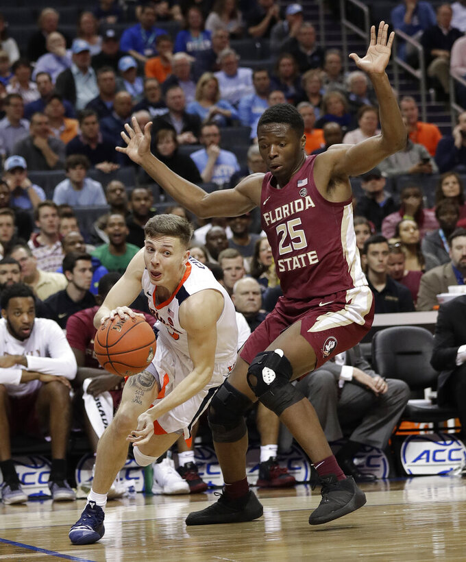 Virginia's Kyle Guy, left, drives past Florida State's Mfiondu Kabengele (25) during the first half of an NCAA college basketball game in the Atlantic Coast Conference tournament in Charlotte, N.C., Friday, March 15, 2019. (AP Photo/Chuck Burton)