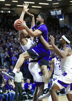 TCU guard Alex Robinson (25) drives against Kansas State forward Levi Stockard III, left, and Kansas State forward Xavier Sneed, right, during the first half of an NCAA college basketball game in Manhattan, Kan., Saturday, Jan. 19, 2019. (AP Photo/Orlin Wagner)