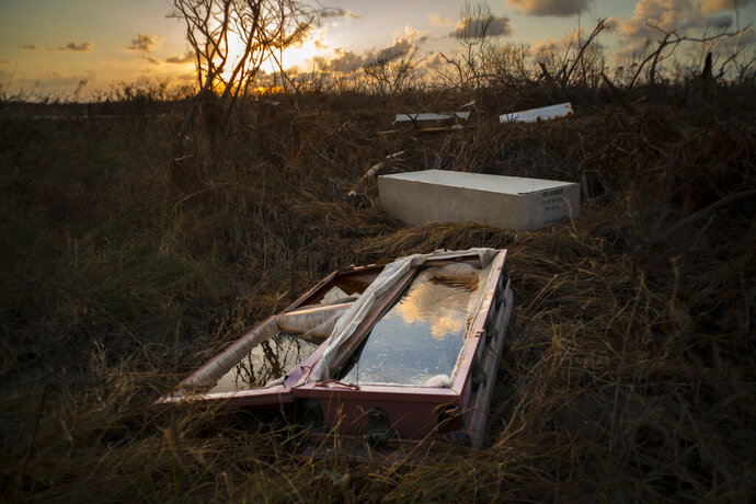 In this Sept. 11, 2019 photo, a shattered and water-filled coffin lays exposed to the elements in the aftermath of Hurricane Dorian, at the cemetery in Mclean's Town, Grand Bahama, Bahamas. Bahamians are tackling a massive clean-up a week after Hurricane Dorian devastated the archipelago's northern islands. (AP Photo/Ramon Espinosa)