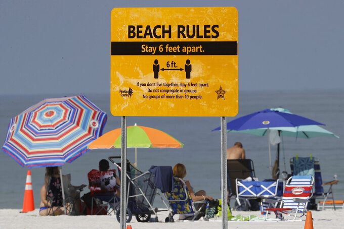 FILE - In this Monday, May 4, 2020 file photo, visitors sunbathe after the beach officially reopened to the public in Clearwater Beach, Fla., after coronavirus restrictions were lifted. The pandemic caught fire in Florida this summer as the state's rapid reopening allowed people to flock to beaches, Disney World, movie theaters and bars. (AP Photo/Chris O'Meara)