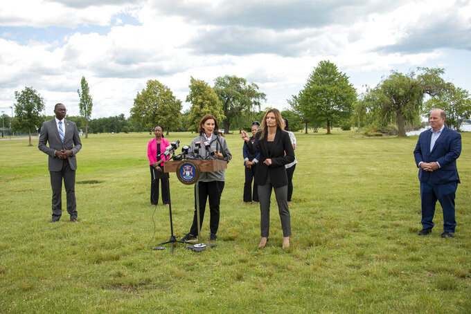 Michigan Gov. Gretchen Whitmer, center, speaks during a press conference on Belle Isle in Detroit, on Tuesday, June 22, 2021, announcing the end of COVID restrictions in the state. After facing 15 months of capacity restrictions and being hit by the country's worst surge of coronavirus infections this spring, restaurants, entertainment businesses and other venues can operate at 100% occupancy starting Tuesday.  (David Guralnick/Detroit News via AP)