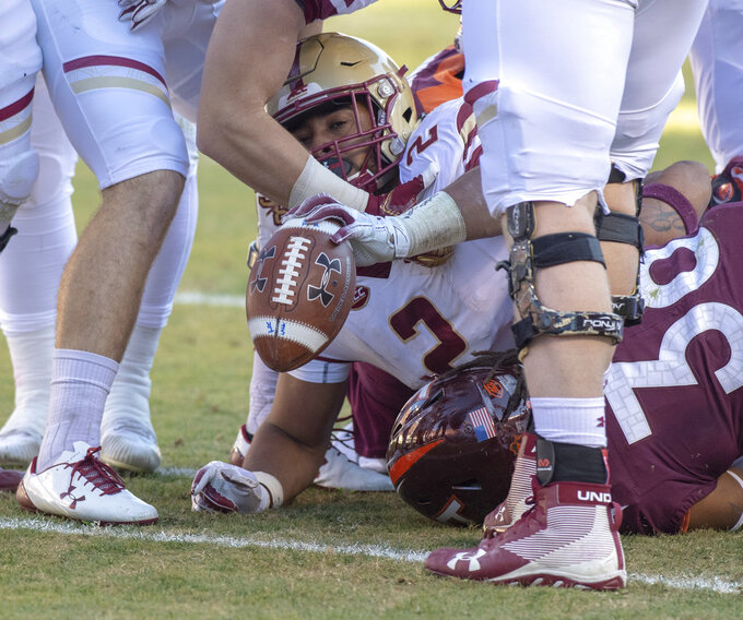 Running back AJ Dillon puts the football in the end zone for a touchdown  during the first half of an NCAA college football game against Virginia Tech in Blacksburg, Va., Saturday, Nov. 3, 2018. (AP Photo/Matt Bell)