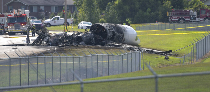 FILE - In this Aug. 15 2019, file photo, the burned remains of a plane that was carrying NASCAR television analyst and former driver Dale Earnhardt Jr., his wife Amy, 15-month-old daughter Isla, two pilots and the family dog lies near a runway at Elizabethton Municipal Airport in Elizabethton, Tenn. Earnhardt Jr. and a pilot struggled to open a crashed airplane's rear exit door as the aircraft began to burn and fill with smoke before the race car driver and his family managed to escape from the main door, according to new details about the 2019 accident released by the National Transportation and Safety Board. (Earl Neikirk/Bristol Herald Courier via AP, File)