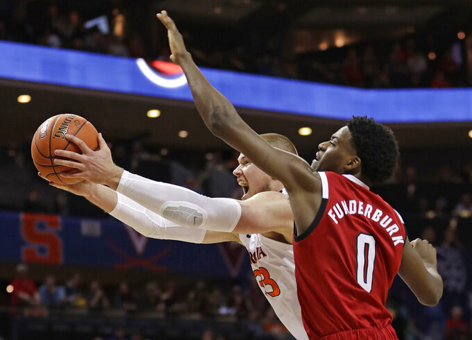 Virginia's Jack Salt (33) grabs a rebound as North Carolina State's DJ Funderburk (0) defends during the first half of an NCAA college basketball game in the Atlantic Coast Conference tournament in Charlotte, N.C., Thursday, March 14, 2019. (AP Photo/Nell Redmond)