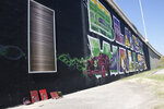 A small memorial to George Floyd is pictured at the foot of a mural of Black Wall St. in Tulsa, Okla., Monday, June 15, 2020, on the other side of what's historically the city's white-black dividing line from where President Donald Trump will rally Saturday. (AP Photo/Sue Ogrocki)