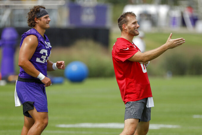 Minnesota Vikings quarterback Kirk Cousins, right, chats while arming up with Jake Bargas (34) during NFL training camp Wednesday, July 28, 2021, in Eagan, Minn. (AP Photo/Bruce Kluckhohn)