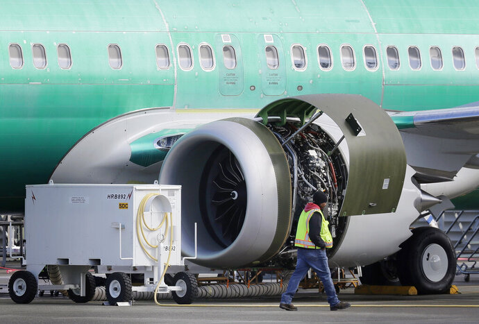 FILE- In this March 13, 2019, file photo a worker walks past an engine on a Boeing 737 MAX 8 airplane being built for American Airlines at Boeing Co.'s American Airlines expects to take a $1 billion hit from two things it didn't expect when 2019 started: That its newest Boeing jet would be grounded for months after two deadly crashes, and that oil prices would rise. (AP Photo/Ted S. Warren, File)