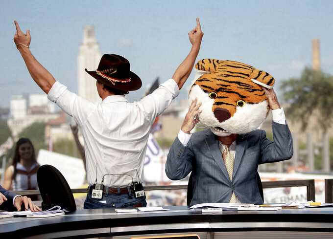 "Matthew McConaughey holds up the ""Hook 'Em Horns"" sign while College GameDay host Lee Corso puts on the LSU mascot head during ESPN's College GameDay broadcast on Saturday, Sept. 7, 2019, in Austin, Texas. (Nick Wagner/Austin American-Statesman via AP)"