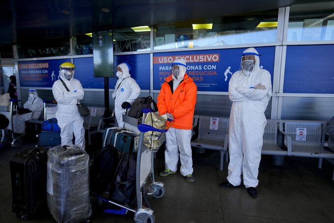 Travelers wait their turn to enter the airport in Buenos Aires, Argentina, Saturday, July 17, 2021. (AP Photo/Natacha Pisarenko)