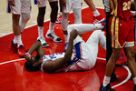 Philadelphia 76ers center Joel Embiid (21) lies on the court before returning to play during the second half of Game 3 of a second-round NBA basketball playoff series against the Atlanta Hawks, Friday, June 11, 2021, in Atlanta. (AP Photo/John Bazemore)