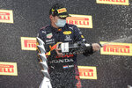 Red Bull driver Max Verstappen of the Netherlands celebrates his victory on the podium of the Emilia Romagna Formula One Grand Prix, at the Imola racetrack, Italy, Sunday, April 18, 2021. (AP Photo/Luca Bruno)