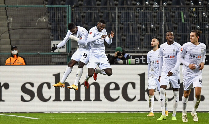 Moenchengladbach's scorer Marcus Thuram, center, celebrates his goal jumping with teammate Breel Embolo, left, during the German Bundesliga soccer match between Borussia Moenchengladbach and Borussia Dortmund in Moenchengladbach, Germany, Friday, Jan. 22, 2021. Moenchengladbach defeated Dortmund with 4-2. (AP Photo/Martin Meissner, Pool)