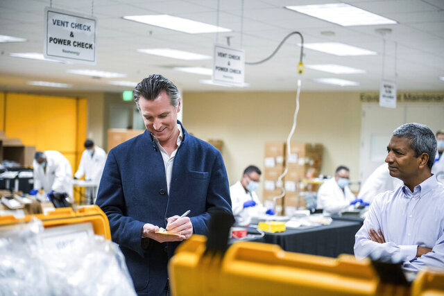 FILE - In this March 28, 2020, file photo, Bloom Energy CEO KR Sridhar, right, watches as California Gov. Gavin Newsom writes down a note during a tour with Sridhar of the Bloom Energy Sunnyvale, Calif., campus. Bloom Energy is a fuel cell generator company that has switched over to refurbishing ventilators as an increasing number of patients experience respiratory issues as a result of COVID-19. Gov. Newsom announced Monday, April 6, 2020, the state would loan 500 ventilators to the national stockpile for use by New York and other states experiencing a crush of coronavirus-related hospitalizations. (Beth LaBerge/Pool Photo via AP, File)
