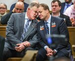 Tim Eyman at right quietly talking with Clint Didier during the court session hearing Friday, Feb. 7, 2020, in Seattle on car-tab measure Initiative 976 which Seattle and others are suing to stop.  (Steve Ringman/The Seattle Times via AP)