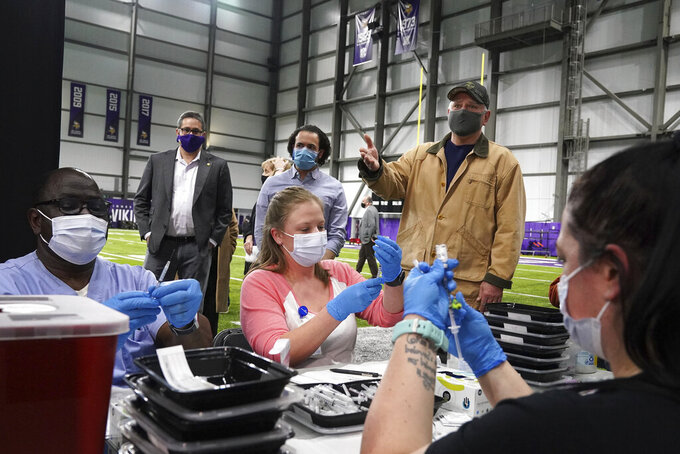 Minnesota Gov. Tim Walz stopped to watch as medical professionals drew doses he took a tour of the Vikings Training Center that'd been converted into a site administering the newly available, single-dose, Johnson & Johnson COVID-19 vaccine Friday, March 5, 2021, in Eagan, Minn. (Anthony Souffle/Star Tribune via AP)