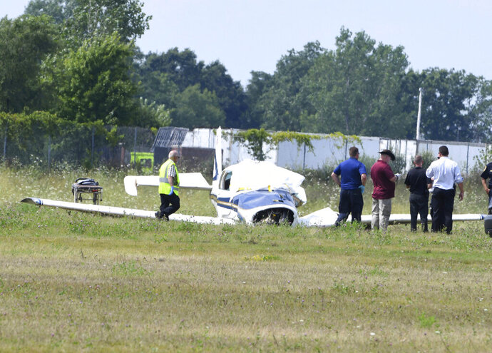 Investigators are on the scene of a small plane crash near the Livingston County Spencer J. Hardy Airport Tuesday afternoon, Aug. 20, 2019. Livingston County Sheriff Mike Murphy says two people were aboard and both were killed. Their names haven't been released. (Daniel Mears/Detroit News via AP)
