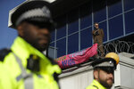 Police Officers stand guard as an Extinction Rebellion demonstrator ties a banner to a raised area at City Airport in London, Thursday, Oct. 10, 2019. Some hundreds of climate change activists are in London during a fourth day of world protests by the Extinction Rebellion movement to demand more urgent actions to counter global warming. (AP Photo/Matt Dunham)