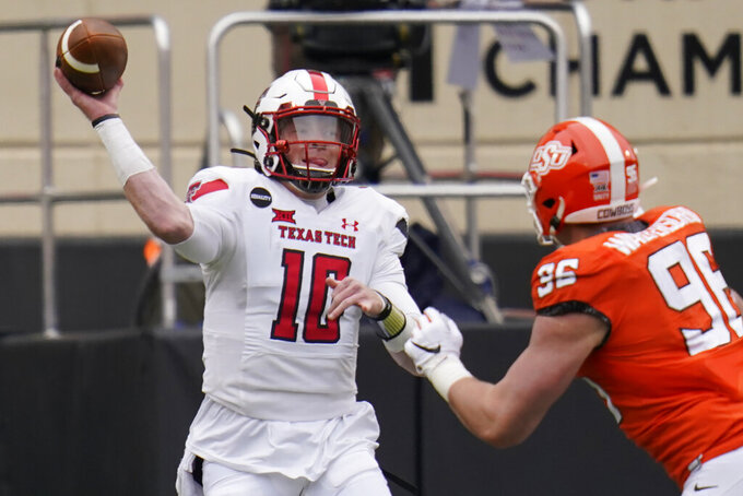 Texas Tech quarterback Alan Bowman (10) throws under pressure from Oklahoma State defensive end Kody Walterscheid (96) in the first half of an NCAA college football game in Stillwater, Okla., Saturday, Nov. 28, 2020. (AP Photo/Sue Ogrocki)