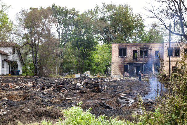 Crews demolish what remains of several buildings that were burned in what authorities deemed as